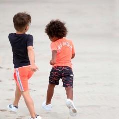 niño con conjunto sturdy manga corta naranja y gris en la playa